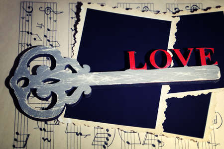 music book: Retro key with word Love and photos paper on music book background