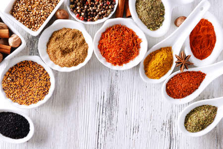 kinds: Different kinds of spices in ceramics bowls and spoons on wooden background Stock Photo