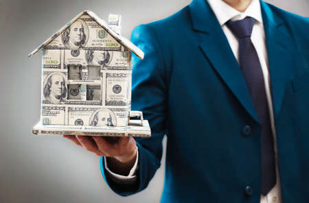 Model of house made of money in male hands on gray background photo