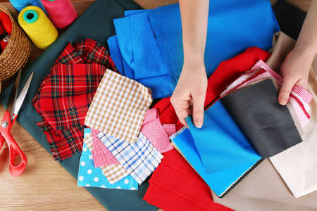 sartorial: Colorful fabric samples in female hands on wooden table background Stock Photo
