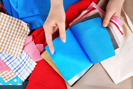 Colorful fabric samples in female hands on wooden table background photo