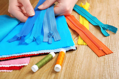 Colorful fabric samples and zipper in female hands on wooden table background photo