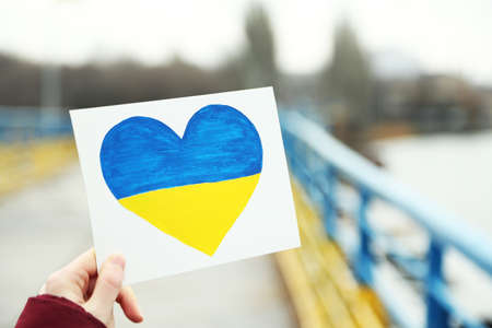 overturn: Hand holding paper heart with painted Ukraine flag