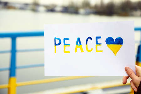 overturn: Hand holding paper with Peace of Ukraine