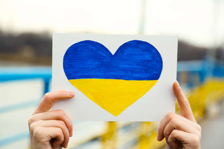 overturn: Hands holding paper heart with painted Ukraine flag Stock Photo