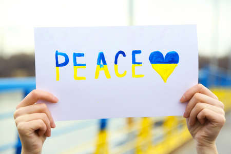 overturn: Hands holding paper with Peace of Ukraine