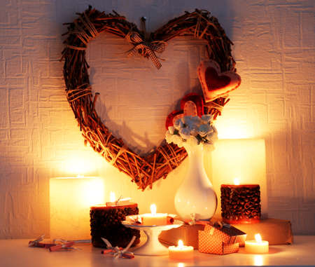 mantelpiece: Romantic still life with wicker heart and candle lights on mantelpiece and white wall background