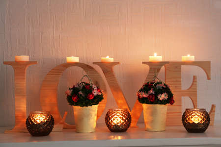 mantelpiece: Romantic still life with word LOVE and candle lights on mantelpiece and white wall background Stock Photo