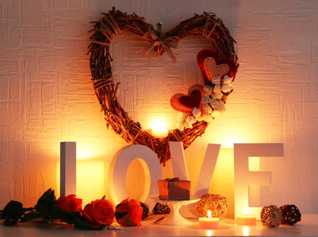mantelpiece: Romantic still life with wicker heart, word LOVE and candle lights on mantelpiece and white wall background