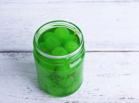 Homemade jar of green maraschino cherry on color wooden planks background Stock Photo