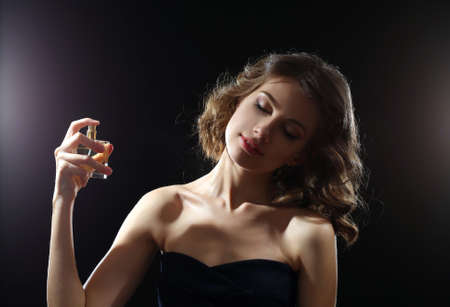 Beautiful woman with perfume bottle on dark background photo