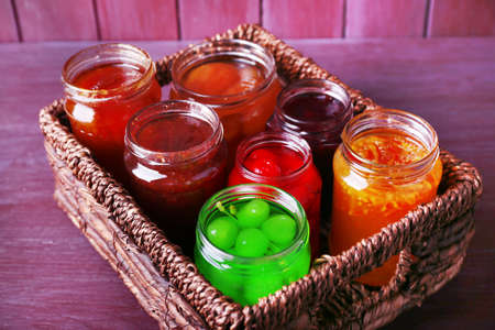 Homemade jars of fruits jam in wicker basket and color wooden background photo