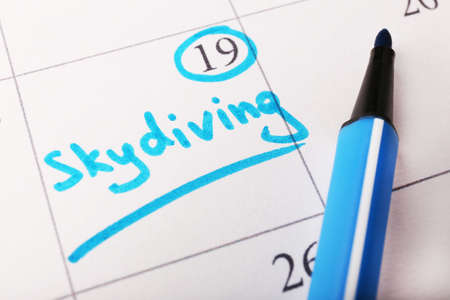 Written plan Skydiving on calendar page background photo