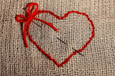 Linen canvas with red heart embroidered on it, close-up photo