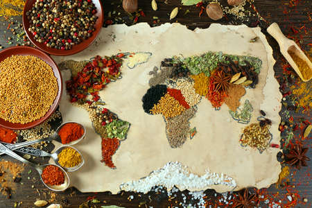 the natural world: Map of world made from different kinds of spices on wooden background
