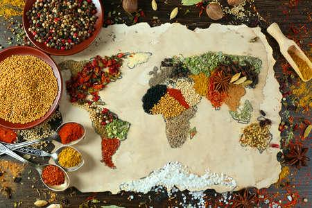 especias: Mapa del mundo hecho de diferentes tipos de especias sobre fondo de madera Foto de archivo