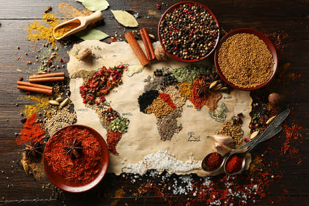 cuisine: Map of world made from different kinds of spices on wooden background