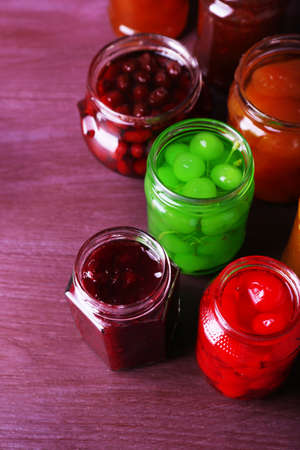 Homemade jars of fruits jam on color wooden background