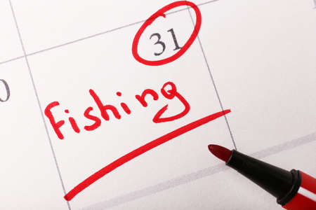 Written plan Fishing on calendar page background photo