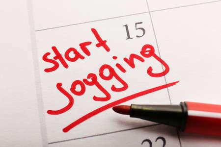 Written plan Start Jogging on calendar page background photo
