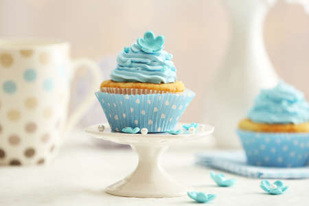 fairy cake: Delicious cupcakes on table on light background