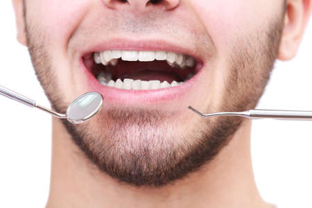 to examine: Examine of young man by dentist isolated on white background Stock Photo