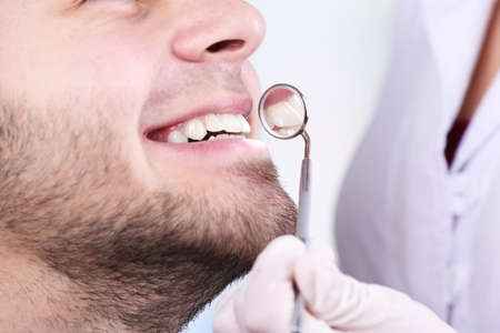 examine: Examine of young man by dentist on white blurred background