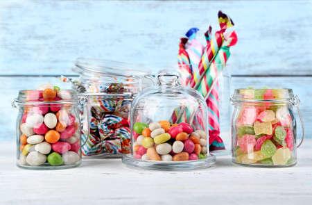 caramelos: Caramelos multicolores en frascos de vidrio de color de fondo de madera
