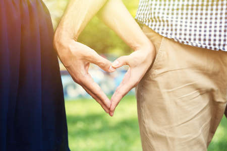 loving hands: Loving couple holding hands in shape of heart, close-up Stock Photo