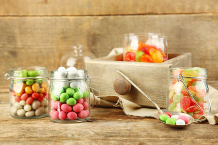 Multicolor candies in glass jars on wooden background Imagens