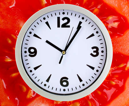 microelements: Food clock with tomato as background. Healthy food concept