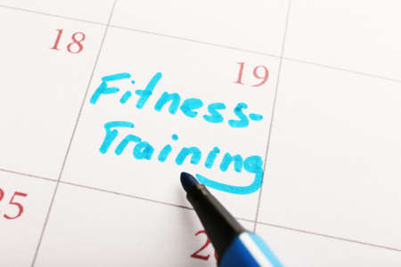 Written plan Fitness Training  on calendar page background photo