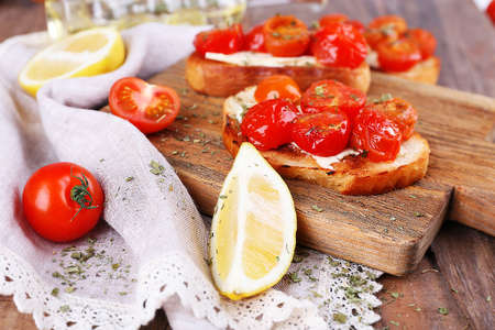 Slices of white toasted bread with canned tomatoes and lime on cutting board on wooden table background photo