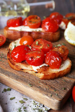 Slices of toasted bread with canned tomatoes and lime on cutting board, closeup photo
