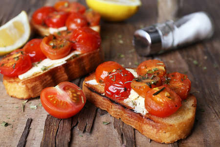 Slices of white toasted bread with canned tomatoes and lime on wooden table, closeup photo