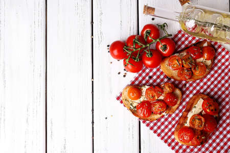 Slices of white toasted bread with butter and canned tomatoes on wooden background photo