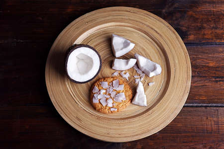 Cookie with cracked coconut on cutting board and rustic wooden table background photo