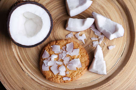 Cookie with cracked coconut on cutting board background photo