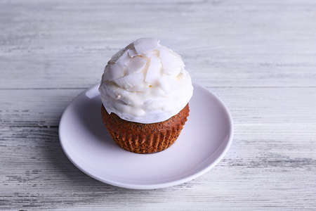 white backing: Delicious coconut cupcake with cream on color wooden table background