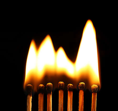 Line of lighted matches on black background Imagens