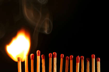 lighted: Line of lighted matches on black background Stock Photo