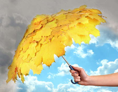 Umbrella  with autumn leaves in hand protecting good weather from dark clouds of rain