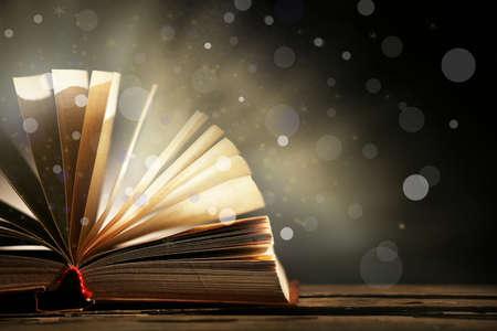 Libro abierto sobre fondo oscuro y brillante Foto de archivo - 39207786