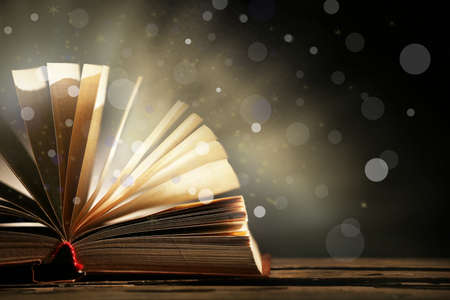 Open book on shiny dark background Stock Photo
