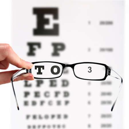 Eye glasses on eyesight test chart background