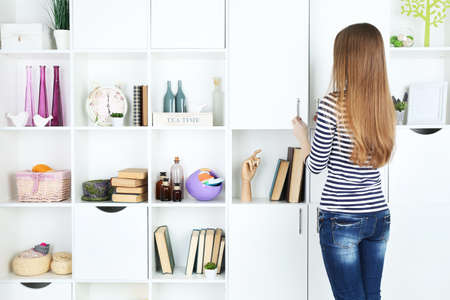Woman looking for something in closet, in room with modern interior photo