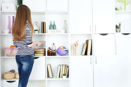 living thing: Woman looking for something in closet, in room with modern interior