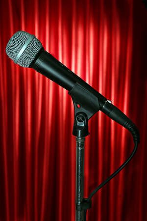 amplified: Microphone on stand on red curtain background Stock Photo