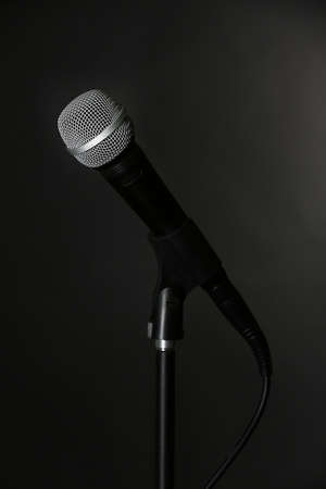 amplified: Microphone on stand on black background Stock Photo
