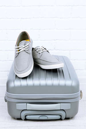 Gray suitcase with male shoes on floor on brick wall background photo